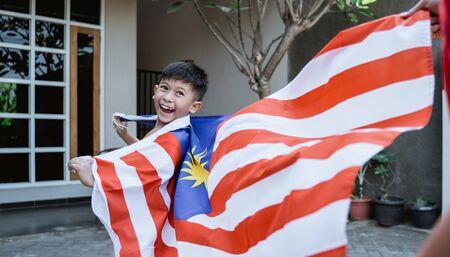 Niño de Malasia con bandera en marcha
