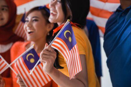 People holding malaysia flag celebrating independence day