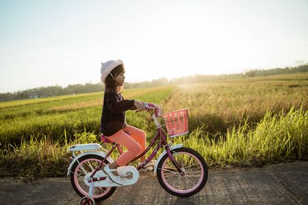 Toddler enjoy riding her bicycle outdoor Archivio Fotografico - 128601535