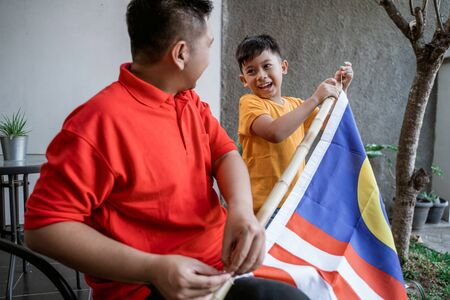 Father and son preparing malaysia flag on independence day