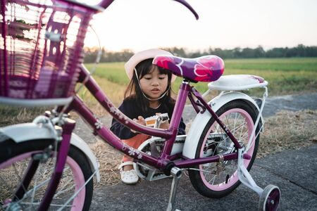 Child try to fix her own bicycle outdoor 版權商用圖片