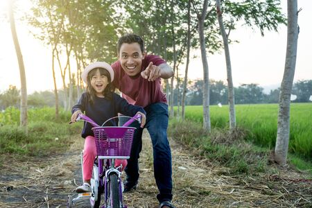 Daughter learning to ride bicycle with daddy 版權商用圖片