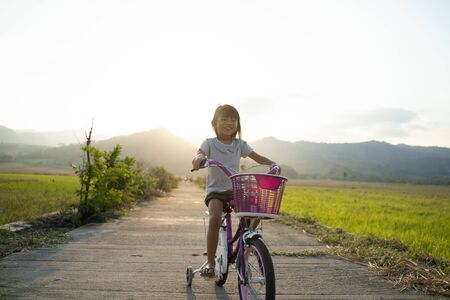 Independent asian child ride her bicycle