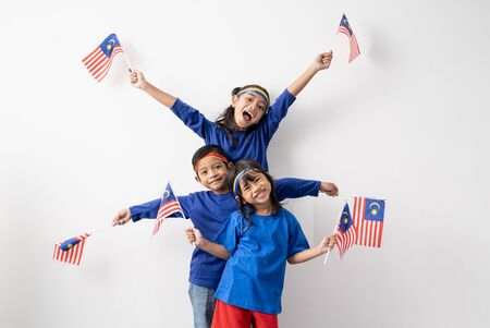 Excited malaysian kids with malaysia flag over white 写真素材