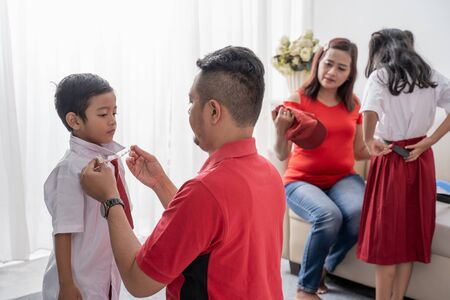 Parent help their children getting ready for school