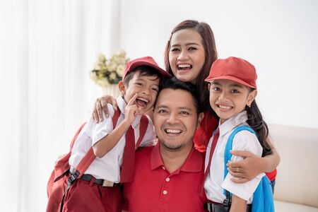 Indonesian primary school student with parents smiling 版權商用圖片