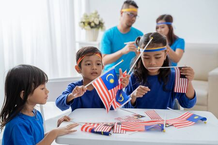 Family creating malaysia flag for independence day