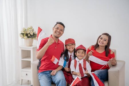 Indonesian family holding indonesia flag over white