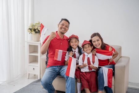 Excited family with indonesian flag raise their arm 写真素材