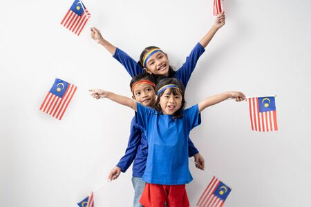 Cute kids holding malaysian flag over white 写真素材