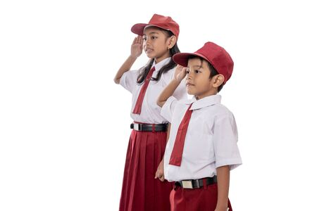 Elementary student wearing uniform giving salute to indonesia flag 写真素材
