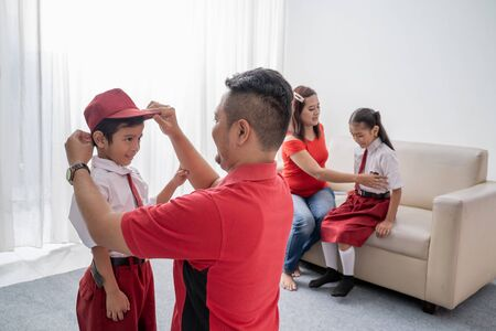 Father help her son getting ready for school in the morning