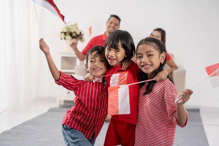 Familia indonesia sosteniendo la bandera de Indonesia sobre blanco Foto de archivo