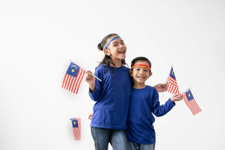 Cute kids holding malaysian flag over white Banco de Imagens