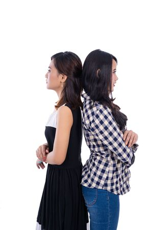 Unhappy two women standing back to back