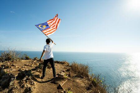 Hombre con bandera de Malasia en la cima de la montaña