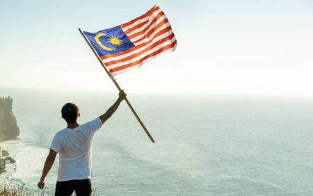 asian man with malaysia flag standing proudly on top of hill