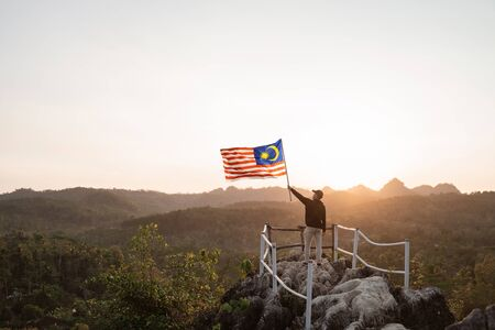 asian man with malaysian flag of malaysia on top of the mountain