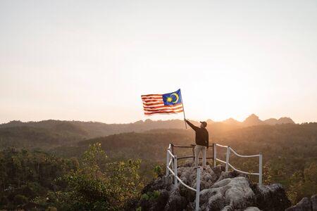 Hombre asiático con bandera de Malasia de Malasia en la cima de la montaña