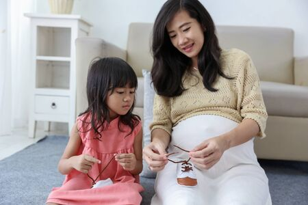 asian girl is fixing the babys shoelaces with her pregnant mother