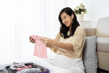 Asian pregnant mother choose some clothes Stok Fotoğraf - 129258003