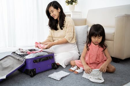 asian little girl holding baby clothes and shoes
