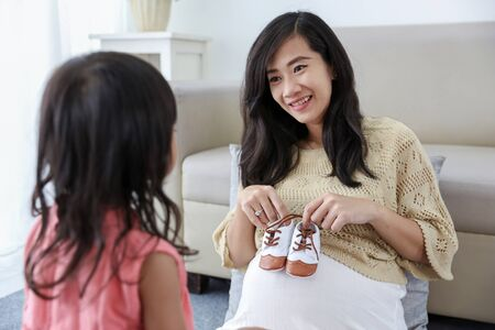 asian pregnant mother holding baby shoes