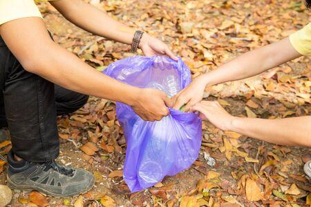Hands of young volunteers cleaning rubbish Banco de Imagens