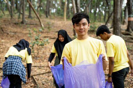 Male smiling volunteer holding trash bag Stok Fotoğraf