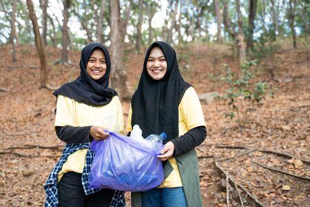 Asian woman hijab volunteer holding trash bag Stok Fotoğraf