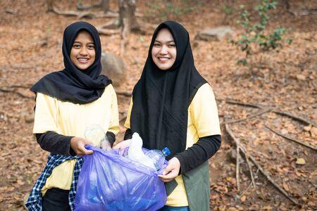 Two woman hijab smiling volunteer holding trash bag