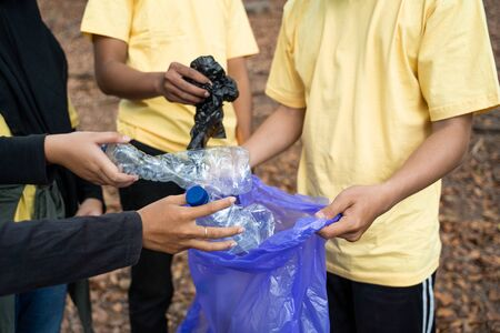 Asian volunteers with garbage bags
