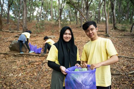Muslim couple smiling volunteer holding trash bag Stock Photo