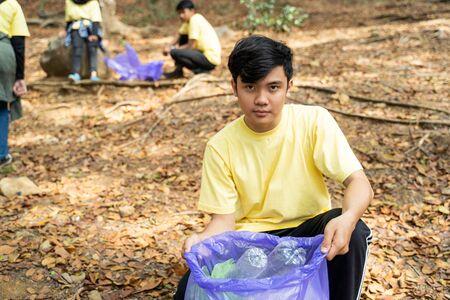 asian man volunteer holding trash bag when squat down Stok Fotoğraf