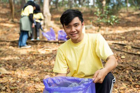 Asian young man smiling volunteer holding trash bag