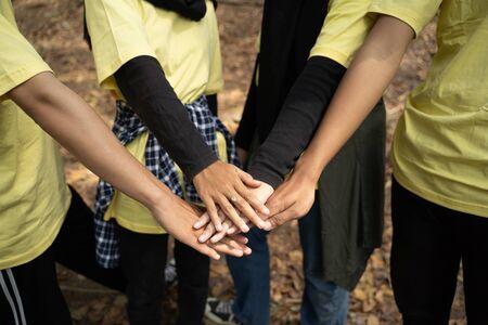 Happy volunteer stacking hands together
