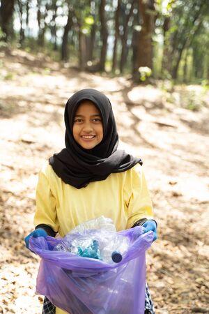 Close up of hijab woman smiling volunteer holding trash bag