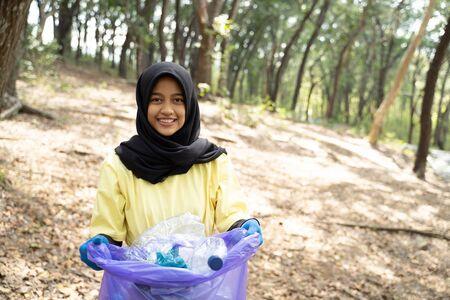 hijab woman smiling volunteer holding trash bag
