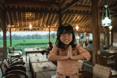 Asian little girl greets in traditional way with both hands Archivio Fotografico