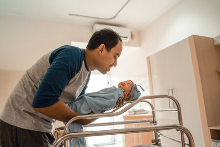 Young smiling father putting his newborn baby Imagens