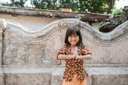 Happy little girl greeting in traditional way from indonesia