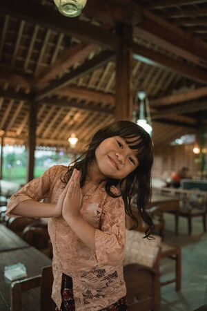 Asian little girl greets in traditional way with both hands Imagens