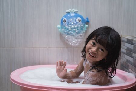 Asian little girl smilling when take a bath with foam