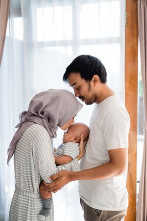 muslim parent with their newborn baby enjoy time together Banco de Imagens