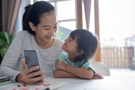 mother and daughter studying trough mobile phone