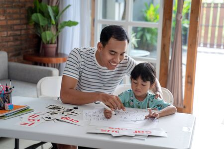 toddler studying with her father at home 写真素材