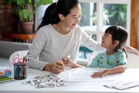 madre enseñando a su hija lo básico a leer y escribir. Foto de archivo