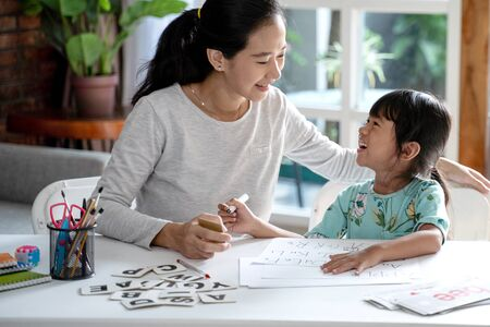 Mutter bringt ihrer Tochter das Lesen und Schreiben bei Standard-Bild