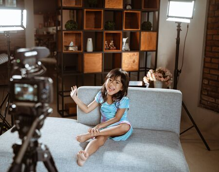asian little girl blogger make review using the camera on foreground Stockfoto