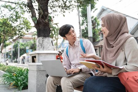 two teenage student holding laptop and book when chatting together